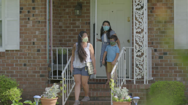 young native-american mother and her two children leave their house wearing protective face masks - veranda stock videos & royalty-free footage