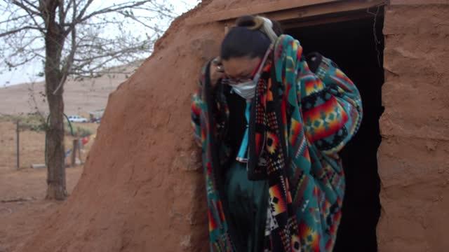 コービッド-19を防ぐためにマスクを着用して彼らのホーガンから歩く若いナバホ家族 - インディアン居留地点の映像素材/bロール