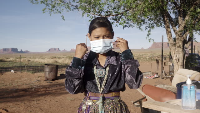 a young navajo girl putting on an n95 mask a mask protecting her from covid19, with monument valley behind her - navajo culture stock videos & royalty-free footage