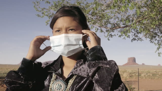a young navajo girl putting on an n95 mask a mask protecting her from covid19, with monument valley behind her - north american tribal culture stock videos & royalty-free footage