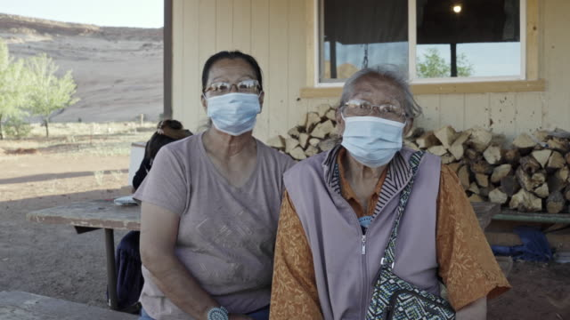 a young navajo man applying hand sanitizer for his grandmother to help protect her from coronavirus - indigenous north american culture stock videos & royalty-free footage
