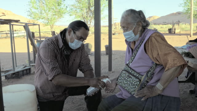 a young navajo man applying hand sanitizer for his grandmother to help protect her from coronavirus - navajo culture stock videos & royalty-free footage