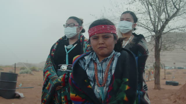 モニュメントバレーの伝統的なナバホ・ホーガンの外でn95フェイスマスクで社会的なディタンシングを表示する若いナバホ兄弟 - ナバホ文化点の映像素材/bロール