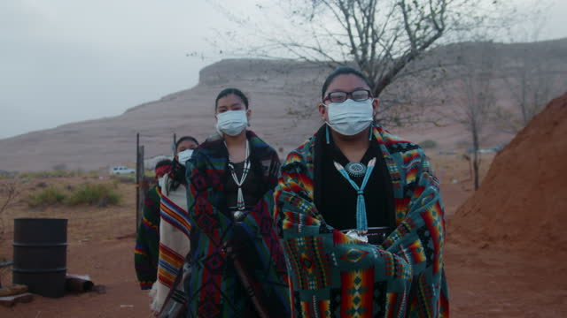vídeos de stock e filmes b-roll de young navajo siblings displaying social distancing with n95 face masks outside their traditional navajo hogan in monument valley - cultura tribal da américa do norte