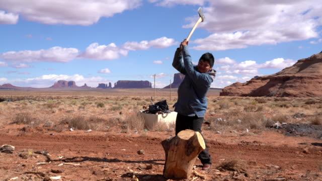 vídeos de stock, filmes e b-roll de um jovem adolescente navajo cortando lenha com um machado - forester