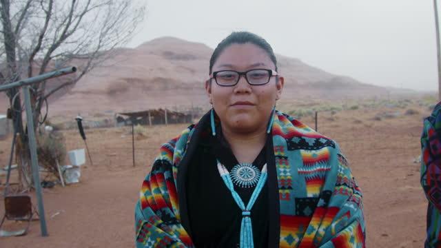 vídeos de stock, filmes e b-roll de jovem navajo mulher de seus vinte anos está em trajes tradicionais em frente de sua casa balançando a cabeça não em navajo country monument valley tribal park arizona - tribo norte americana