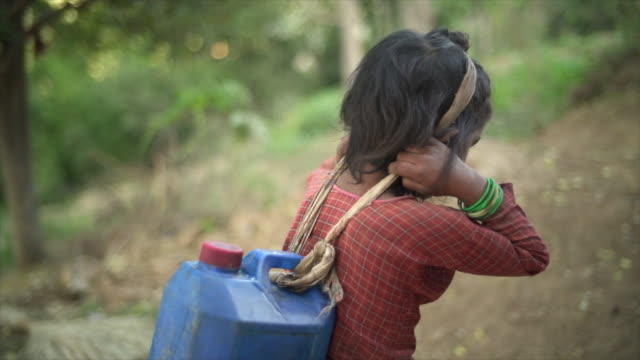 young nepali girl carries large jug of water - povertà video stock e b–roll