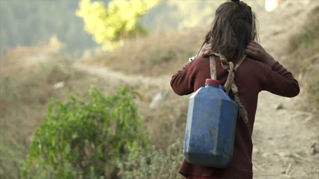 young nepali girl carries water jug with head strap - jug stock videos & royalty-free footage