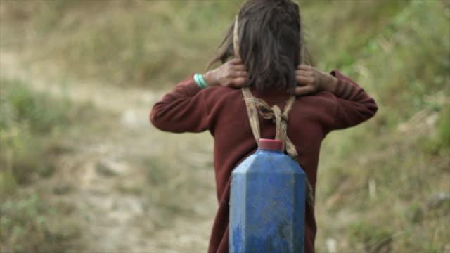 Young Nepalees meisje draagt Waterkaraf met hoofd riem