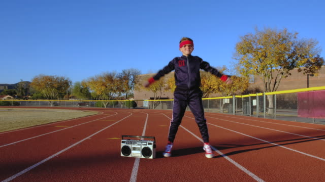 young nerd boy at track doing jumping jacks - portable stereo stock videos & royalty-free footage