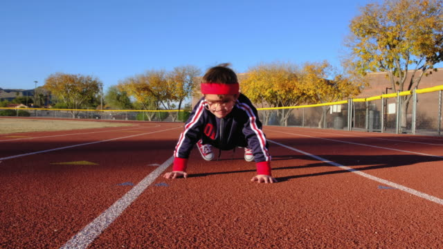 young nerd boy at track doing pushups - push ups stock videos & royalty-free footage