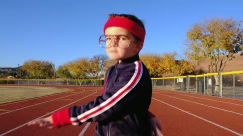 stockvideo's en b-roll-footage met jonge nerd jongen op track opwarmen - bril brillen en lenzen