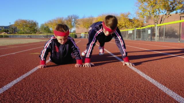 vídeos de stock e filmes b-roll de young nerd boys at track doing pushups - flexão de braço