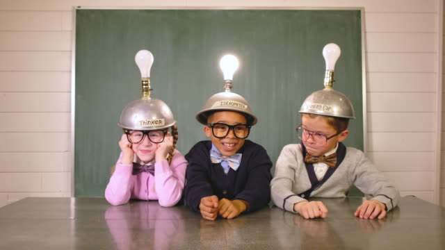 young nerds think while wearing idea helmets - immaginazione video stock e b–roll