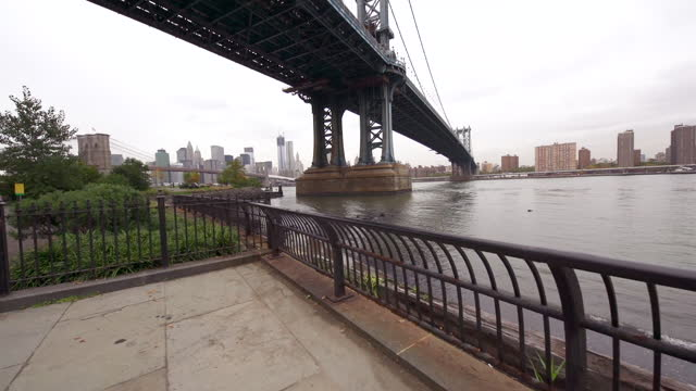 Young New York couple walk away from Manhattan Bridge holding hands along the East River