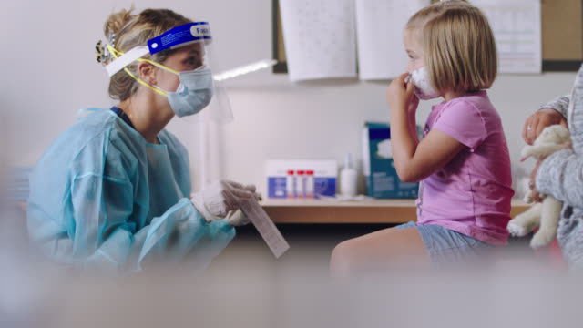 young nurse in medical clinic tests cooperative girl for covid-19 using a cotton swab - glove stock videos & royalty-free footage