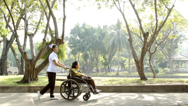 Young nurse take caring old woman on wheelchair