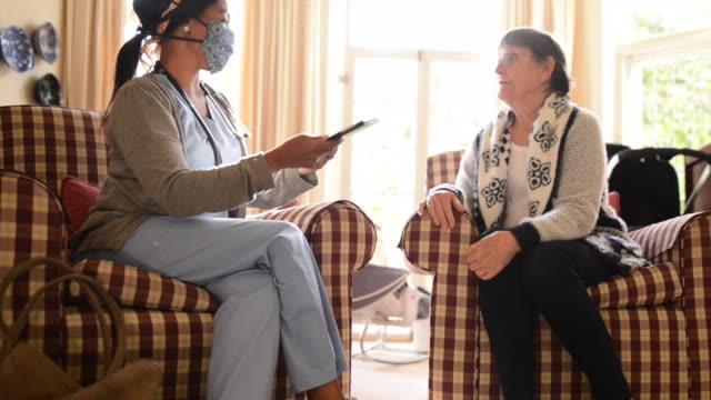 young nurse talking with a senior patient in her living room at home - chair stock videos & royalty-free footage