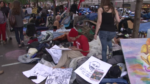 young occupy wall street protesters camp out and make posters in zuccotti park in lower manhattan. - occupy protests stock videos & royalty-free footage