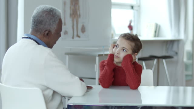 a young of elementary school age confides in her doctor. - human heart stock videos & royalty-free footage