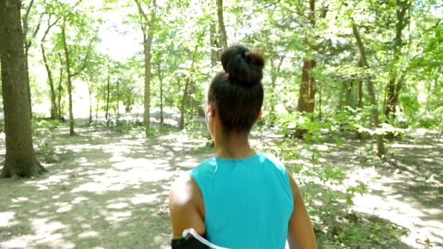 young off road runner jogging on dirt path in sunny wooded park - hair bun stock videos & royalty-free footage