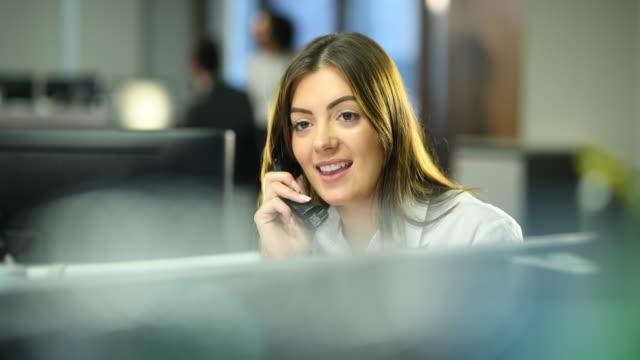 junge büroangestellte im gespräch mit kunden am telefon - rat stock-videos und b-roll-filmmaterial
