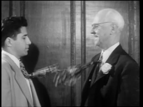 b/w 1946 ms profile young + old businessmen facing each other with waving ties - moving image stock videos & royalty-free footage