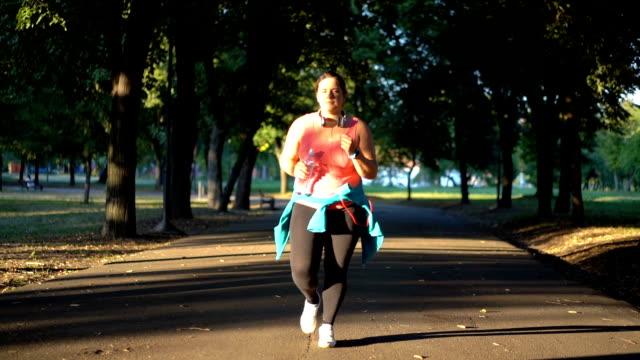 走っている若い太りすぎの女性 - パワーウォーキング点の映像素材/bロール