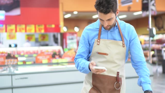 young owner / employee using mobile phone at supermarket - apron stock videos & royalty-free footage