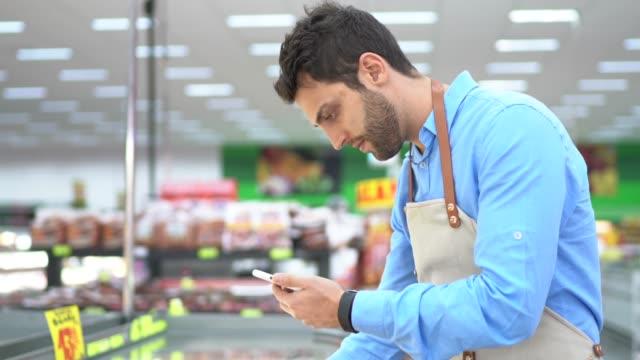 スーパーマーケットで携帯電話を使用して若い所有者/従業員 - メガストア点の映像素材/bロール