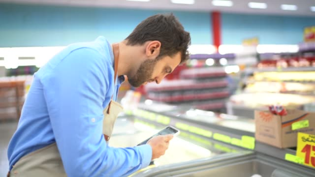 young owner / employee using mobile phone at supermarket - assistant stock videos & royalty-free footage