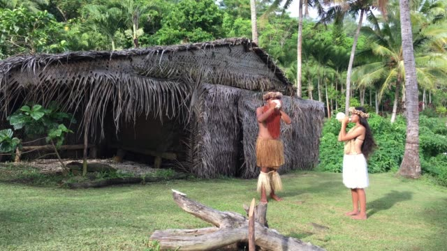 Young Pacific Islander man and woman blowing conch shells in a Maori village in the highlands of Rarotonga Cook Islands