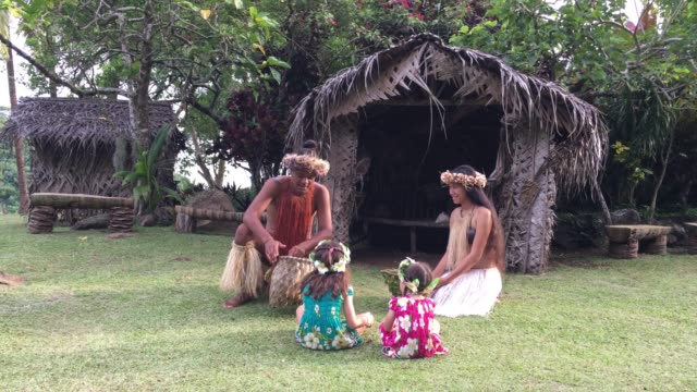 Young Pacific Islander man and woman talks to tourist girls in a Maori village in the highlands of Rarotonga Cook Islands