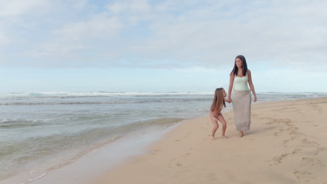 young pacific islander mother and daughter walking along beach - pacific islander stock videos & royalty-free footage