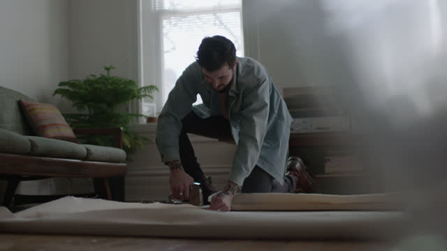 vídeos y material grabado en eventos de stock de ws slo mo. young painter folds and staples stretched canvas over wooden frame on apartment floor. - reforma