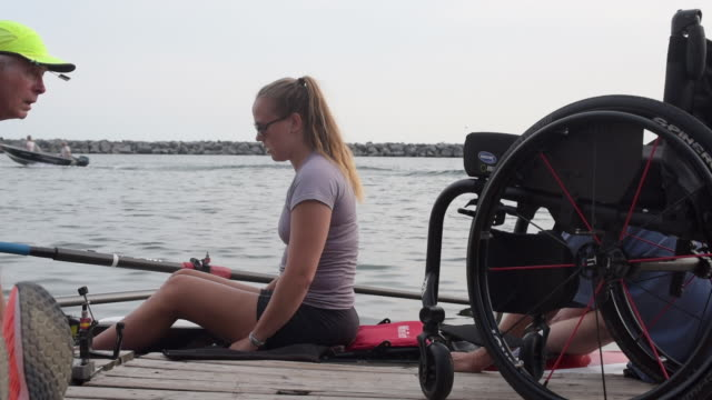 Young paralyzed woman getting into row boat.