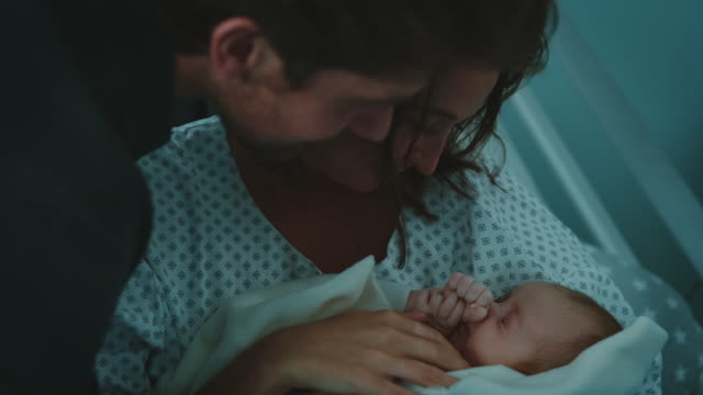young parents admiring newborn baby in hospital - admiration stock videos & royalty-free footage
