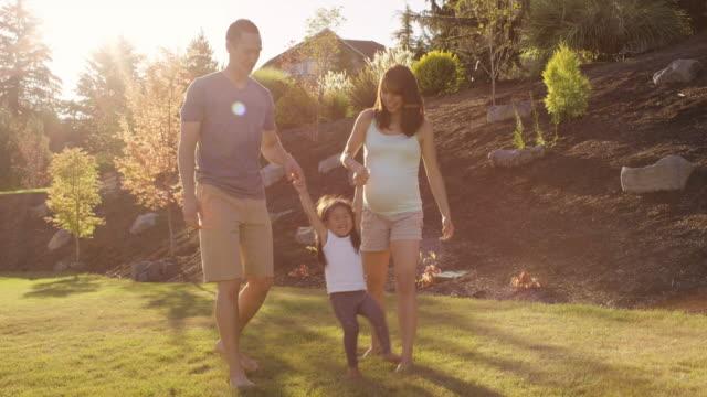 裏庭で娘と遊ぶ若い親 - 継父点の映像素材/bロール