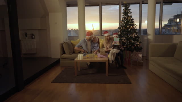 young parents surprising their children with gift boxes while spending christmas at home. - decorazione festiva video stock e b–roll