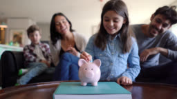 Young parents teaching their kids to save money in a piggy bank on foreground all smiling