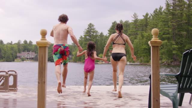 stockvideo's en b-roll-footage met jonge ouders met dochter lopen en springen van dok in lake - stilstaand water