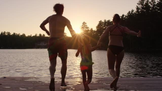 Unga föräldrar med dotter kör och hoppa från docka i sjön