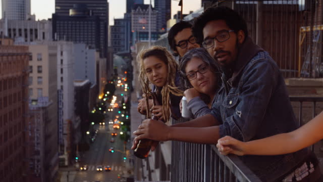 Young Partygoers Leaning Over Balcony
