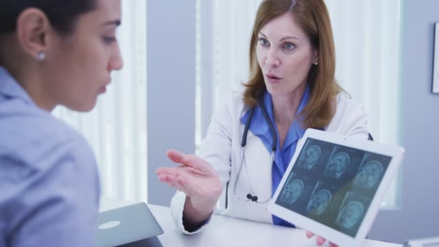 young patient consulting with doctor over ct-scan indoors medical clinic - 女性患者点の映像素材/bロール