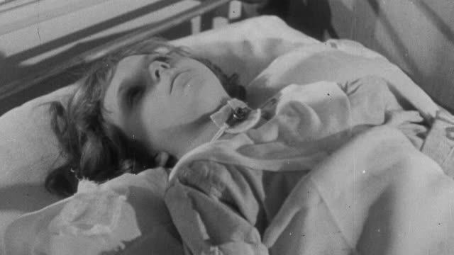 1941 zo a young patient in the fever hospital suffering from diphtheria, with a hole cut in her windpipe so she can breathe / united kingdom - diphtherie stock-videos und b-roll-filmmaterial