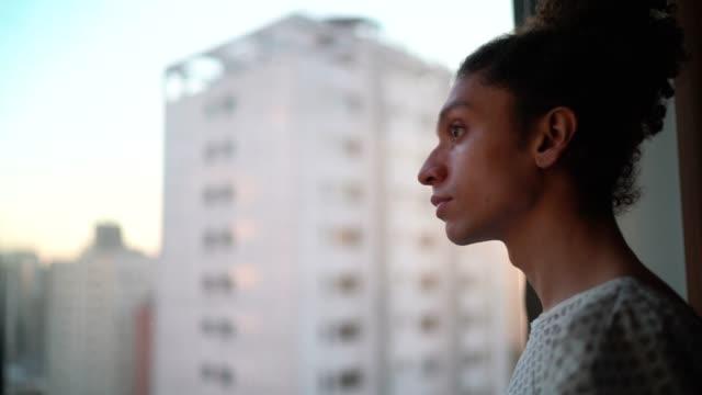vidéos et rushes de jeune patient regardant par la fenêtre à l'hôpital - brésilien