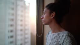 Young patient looking through window at hospital