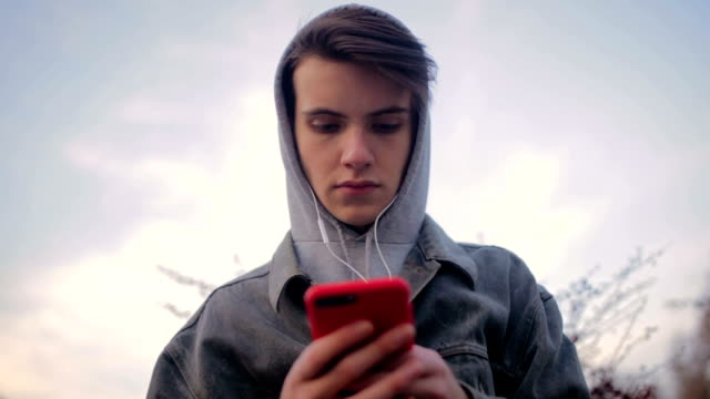 young people and emotions concept. sad hooded man teen boy with headphones - teenage boys stock videos & royalty-free footage