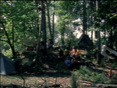 / young people at gathering for 'celebration of life' festival / young man sleeping in hammock by river / campsites on riverbank / young man... - hippie bildbanksvideor och videomaterial från bakom kulisserna