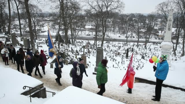 Young people bearing flags walk among graves while honoring Reinstatement Act signatories buried at Rasos Cemetery while celebrating the 100th...